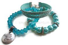 www.dekralentuin.nl Handgemaakte set van blauwe/turquoise armbanden. De volgende materialen zijn o.a. gebruikt: facetkralen, glaskralen, glasparels, spacers, suede met studs, hanger/bedel met tekst