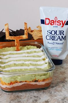 Daisy 7 Layer Dip for Super Bowl - 7 Layer Dip is a classic for parties.  This one gets a little football theming with a tortilla goal post and easy field striping using Daisy Squeeze Sour Cream.