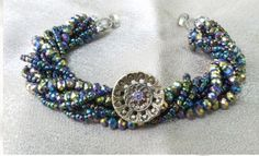 Antique button bracelet showcasing beautiful antique button, set on strands of iridescent crystals and seed beads. Magnetic clasp