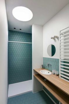 Modern matte muted green tile in bathroom with light wood vanity and round mirror
