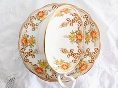 Here is a gorgeous 1930s Royal Albert Crown China teacup and saucer. A beautiful pattern of yellow and orange flowers with gold scrolls and trim. The cup is 2 1/2 in tall and the saucer is 5 1/2 in diameter. There are no chips, cracks or crazing. Items in my shop are vintage and not