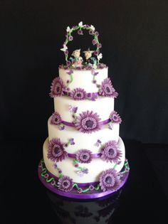 Wedding cake in violet with marguerite in violet. Topper with small dragons
