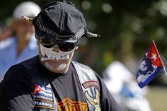 """Masked Harley owner Camilo Sanchez participates in Cuba's first national gathering in honor of the Harley Davidson motorcycle in Varadero, Cuba, Saturday April 14, 2012. Cuba's """"Harlistas"""" are just as passionate as their American counterparts, but like the owners of rumbling 1950s Detroit classic cars that still prowl the streets of Havana, vintage Harley fans have had to get creative to keep their bikes road-worthy. (AP Photo/Franklin Reyes)"""