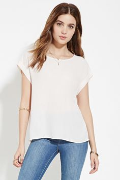 This crepe woven top flaunts a boxy silhouette with a round neckline and cuffed short sleeves.