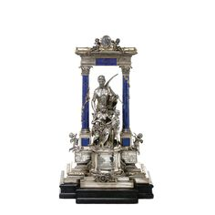An Austro-Hungarian silver and lapis sculptural presentation piece, Vienna, circa 1900 resting on an angular wood plinth, the stepped base applied in gilt with a foliate scroll border and an industrial trophy to the front, the lower part applied to the front and sides with plaques of a steel plant and iron and steel rollers and workers, the reverse embossed in relief with men labouring at a furnace, below a sculptural group of a wasted labourer with a pickaxe and jacket slung over his…