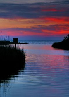 The last rays of the setting sun streak the sky over Pamlico Sound, on the Outer Banks of North Carolina (by Steven Ainsworth)
