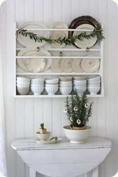 Holiday decor and inspiration. Beautiful white platerack with white dishes above a vintage dropleaf table.