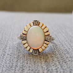 This Stunning Antique Ring features a 10K Antique Gold Setting with 1.3 carat Natural Opal and 4 Natural Antique Rose Cut Diamonds measuring .06