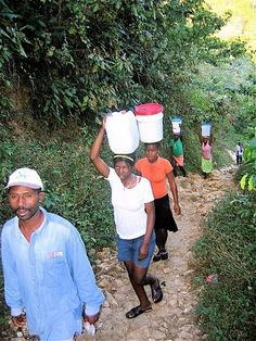 Women balancing buckets of water or clean, wet clothes on their heads, coming from river near Thiotte, Haiti. Nadia & Bijou make this trip with other ladies in one scene in Pearl of the Caribbean, second Island Legacy Novel. Haiti And Dominican Republic, Reading Projects, Water Bucket, Buckets, Caribbean, Novels, Scene, Pearl, River