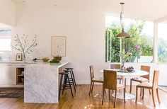 The open dining area suits the couple's entertaining style, with a carrara marble waterfall counter and round wood dining table.