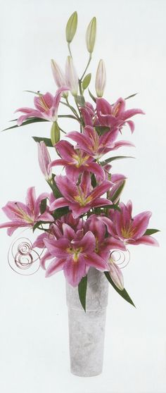 Presented in a narrow triangular styling, this grand gathering of Oriental Lilies appears to be an amazing single stem that is completely alight with luminous blossoms. – @FloristsReview