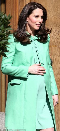 The Duchess placed a hand on her bump as she left the symposium...
