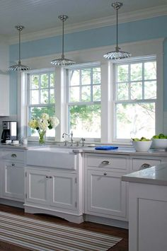 Light beach and shell tones with farmhouse sink in this coastal kitchen