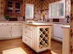 Eine kleine Creme farbigen Kücheninsel mit Butcher Block oben und Kreuz und quer durch Weinregal steht im Mittelpunkt dieser winzigen Küche.