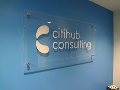 Custom clear acrylic / clear plexiglass panel with flat die-cut digital graphic logo in opaque white, mounted with 4 corner polished stainless steel standoffs onto interior painted blue drywall in NYC. For more information on office signs, visit http://www.SignsNewYork.net