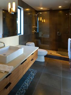 dark bathroom tile with pebble border, teak wood, glass door and light pebbles on shower flor