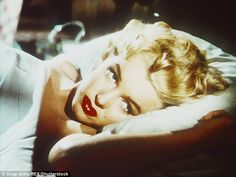 Her inspiration? Marilyn Monroe often posed in a bed with white sheets; here she is seen f...