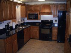 Cherry Kitchen Cabinets Black Granite medium wood cabinets + white subway tile blacksplash + dark