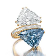 'THE BVLGARI BLUE'. A TWO-STONE COLORED DIAMOND AND DIAMOND RING, BY BVLGARI. Set with a triangular-cut fancy vivid blue diamond, weighing approximately 10.95 carats, and a triangular-cut diamond, weighing approximately 9.87 carats, to the baguette-cut diamond half-hoop, mounted in gold, circa 1972. Signed. Price Realized $15,762,500 // Estimate on request. GIA / 10,95 - Fancy Vivid Blue, Natural Color, VS2 clarity // 9,87 - G color, VS1 clarity [C. JEWELS - 20 October 2010 - NY]