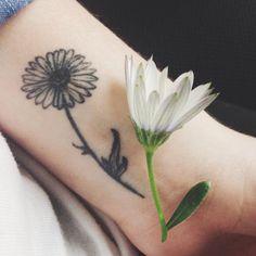 Small wrist tattoo of a daisy on Clara.