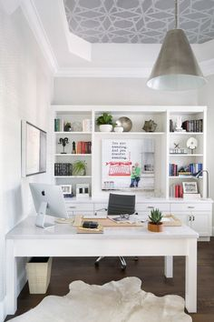A quartz-topped desk and custom cabinetry with open shelving by Rachel Eve Design provide ample workspace and storage in the office | archdigest.com