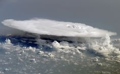 a fully formed anvil cloud. Numerous smaller cumulonimbus towers and cloud shadows are visible in the image.