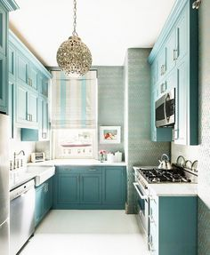 Galley kitchen with dusty blue cabinets printed wallpaper and a silver pendant light