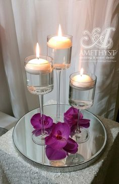 Trio Stem cylinder vases with floating candles & purple orchids on diamante mirror plate. #decorhire #centrepiece #weddingdecor #simple #elegantwedding