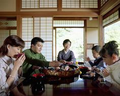 Daily Life: This is a photo of a Japanese family eating. Japan has a very different eating manner than we do in the US. Drinking soup directly from a bowl, or making slurping sound is not impolite, like it is here in the US. Bowls are used most of the time when eating, and are held at chest level. Chopsticks are almost always used, and the main meal of the day is dinner, but can be eaten later in the evening than here in the US because the men in the family work very late.