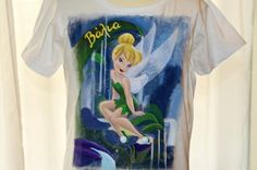 Hand painted girl's t shirt, featuring Tinkerbell seated on a leaf. A girl's name (Valia) is written in Greek. The colors are non-toxic, water based, permanent fabric colors. The Girl Who, Girl Names, Gifts For Girls, Tinkerbell, To My Daughter, Cotton Fabric, Hand Painted, Colours, Drawings