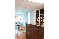 Placares de madera laqueada con puertas de vidrio (Johnson Acero) y, en el centro, cajonera con tapa vidriada, un diseño del Estudio GG&A (Carpintería Palo Rosa).  /Magalí Saberian