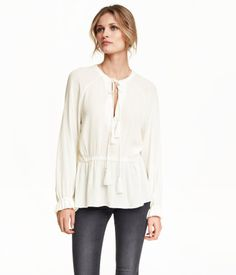 White. Long-sleeved blouse in airy, crinkled fabric. Drawstring with decorative tassels at neck, and elastication at waist and cuffs.