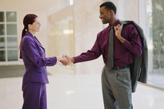 Businessman and businesswoman shaking hands in lobby, profile
