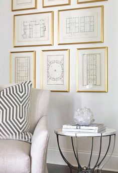 Chic living room features a reading corner filled with a gray linen accent chair lined with a Mary McDonald Vanderbilt Velvet Dove Pillow  and a round metal and marble accent table placed before a wall lined with blueprints in gold leaf beveled frames.