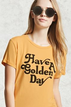 "A knit tee featuring a ""Have A Golden Day"" text front graphic, a round neck, and short cuffed sleeves."