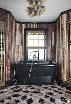The master bath walls are covered in onyx fantastico, and the flooring is marble and onyx; the sconces are vintage.   - ELLEDecor.com