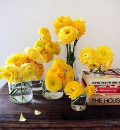 Luxe Impression - Take a small bouquet of single-colored in-season flowers, like golden yellow ranunculus and up the visual impact by splitting up the blooms among various clear containers