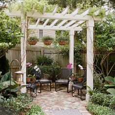 Simple seating and hanging baskets for this painted pergola