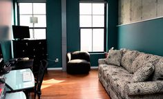 Office in a condo with a contemporary and industrial style. Blue walls with exposed concrete and bamboo floors. Floor to ceiling windows. Includes a black and white, floral print couch.