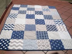 This stunning nautical themed patchwork baby quilt measuring 36 by 48 in grey and navy blue featuring anchors and waves as well as chevrons, polka