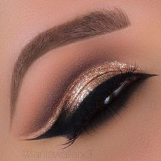 Gold eye makeup with a dramatic eyeliner.