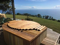 Redwood hot tub, seated in a deck, with a wooden roll-top cover.