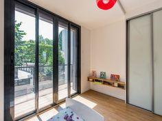Une chambre d'enfant ouverte sur le jardinavec grandes verrières