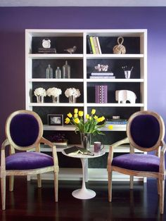 Eggplant purple sitting area with white bookcase and yellow flowers
