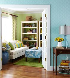 Blue and greens!  These colors make me feel at home.  I love the blue hallway and the doors that open into the green living room or sitting area.  The bookcases are open or the backs are also painted green which I love. The ottoman, side table, and pillows do a great job puling these two spaces together. I also stack books under tables and think it is a great way to make a house your home.