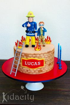 A Fireman Sam cake for his fan, little Lucas. The figures are gumpaste, as are the flames. The ladder is polymer clay for durability (and I wasn't sure about the limitations of sugar! The customers only request was that she wanted Norman. Fireman Sam Birthday Cake, Fireman Sam Cake, Fireman Party, Fire Cake, Fire Fighter Cake, Character Cakes, Just Cakes, Novelty Cakes, Cakes For Boys