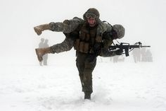 2015 Year in Pictures : A soldier carrying his battle buddy who is holding an M16 model A2, a military-grade assault rifle, in the snow.