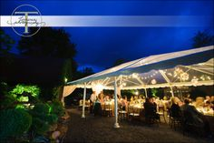 An evening outdoor wedding reception - tent with lights.