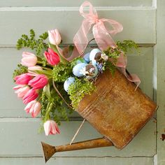 Spring Watering Can with Flowers:  Filling a rustic watering can with pink tulips, greenery, & pastel blue eggshells is the perfect decoration for spring. Stuff the watering can with floral foam to secure the stems. When you're finished creating the arrangement, wire it to your front door and cover the wire with ribbon.  Tip: To keep flowers fresh, put the stems in water vials.
