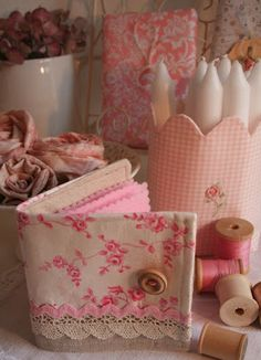 A pretty pink needle case and vintage wooden spools